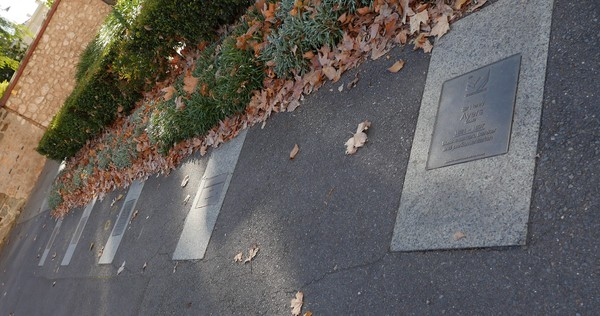 Image: row of bronze plaques embedded in footpath