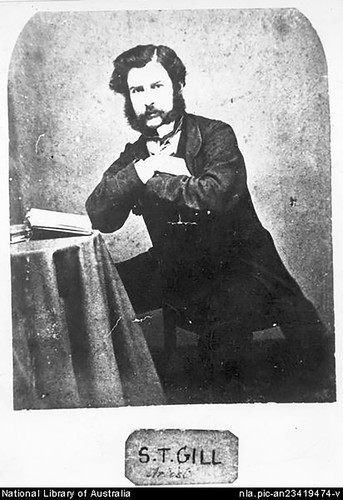 Image: Black and white photograph of a man seated backwards on chair with arms crossed on seat back and an open book on the table beside him