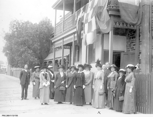 Image: A group of women and men in Edwardian attire stand in front of a two-storey stone building with flags hanging from the second-floor verandah