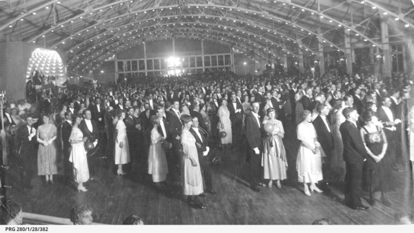 Image: a crowd of men and women wearing 1920s era clothing stand in pairs in a large hall the ceiling of which is decorated with lines of small lights.