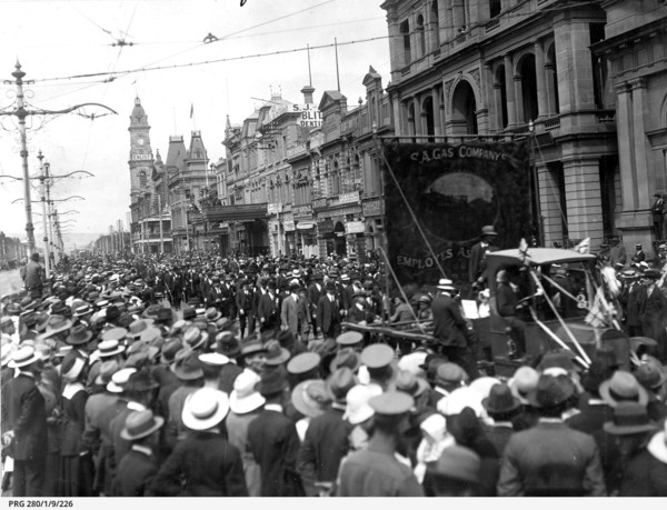 Image: crowd gathered to watch a procession along a street, large banner in centre