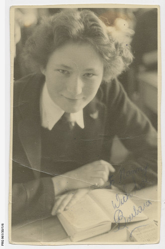 "Image: Photographic portrait of a young woman in school uniform. She has a book open in front of her. The photo is inscribed in blue pen: ""To Nanny, With Love, Barbara"""