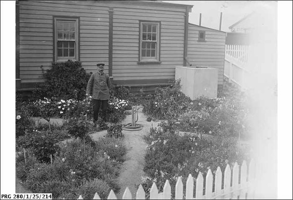 Image: A man in uniform stands in a flower garden next to a cottage