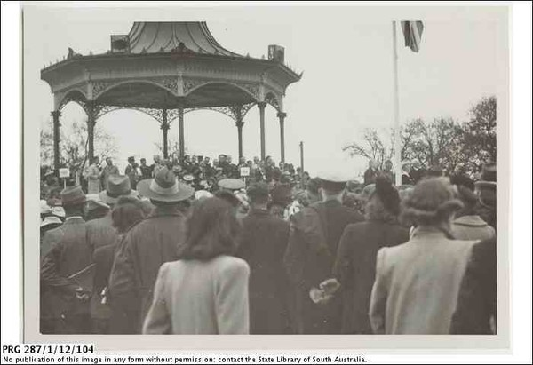 Image: a crowd of people, some in military uniform, watch dignitaries give speeches from a rotunda. A flag, possibly the Union Jack, is just visible on a flagpole to the right of the photograph.