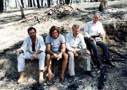 Image: four men sitting in burnt out bushland