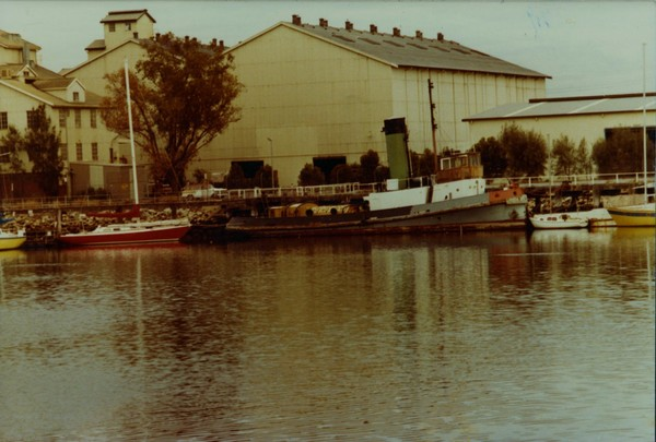 Image: A derelict tugboat is moored against a wharf next to a large complex of buildings. A number of other small boats are also moored at the same wharf