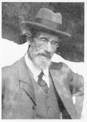 Image: A photographic portrait of an elderly Caucasian man wearing an Edwardian-era suit and hat. He has a white full beard and is wearing wire-rimmed spectacles