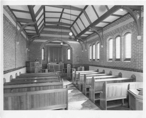Image: The interior of a Christian chapel constructed from brick. It is an austere structure that features two lines of simple wooden pews and a small wooden altar