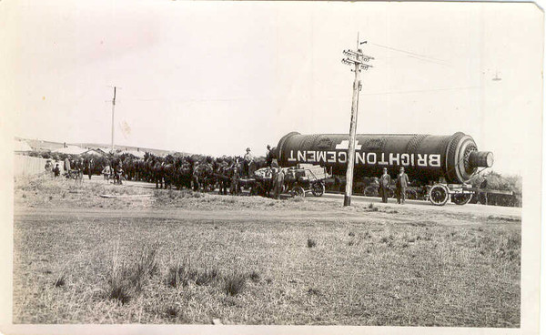 Image: A massive iron cylinder with the words 'Brighton Cement' painted on its side is pulled by several horses