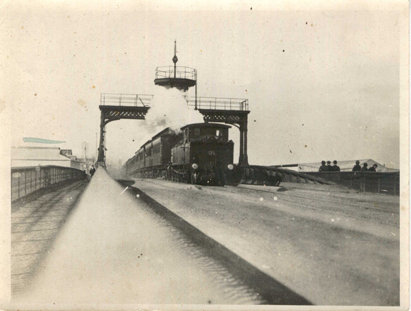 Image: A steam train passes beneath an observation tower on a bridge. A group of men in Edwardian attire perambulate along a walkway on the side of the bridge
