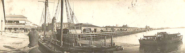 Image: A motor vessel gets underway from a wooden jetty. The waterfront of a port town is visible in the background