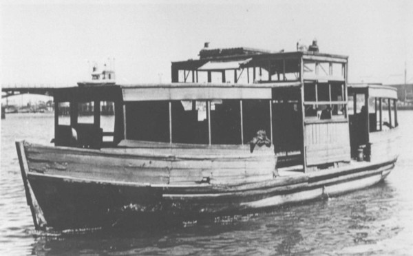 Image: A wooden-hulled motor boat transits between two points on a narrow river. The hull of the boat is in poor overall condition, and the vessel looks derelict