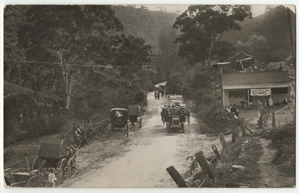 Image: old cards, dirt road, paddocks and hut
