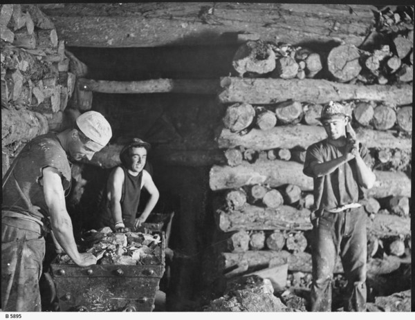 Image: Three men working inside a mine shaft with stacked timber walls and ceiling, and two trolleys filled with stone materials