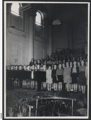 Image: A large choir of children singing with a piano in the foreground.
