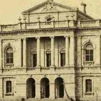Image: a large stone public building with a three arched entrance above which is a balcony with columns. A smaller third storey with a gable roof rises from the centre of the building. Two storey wings extend to either side.