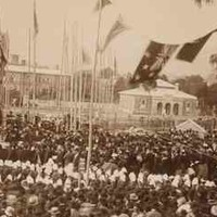 Image: a huge group of people in 1880s dress and hats surround a stage where a foundation stone is being laid.