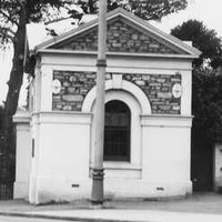 Image: Small stone building with a single arched window and gable roof next to open gates. A man stands next to the gates