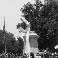 Image: crowd of people surrounding large bronze statue with cloth being removed.