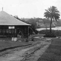 Image: a round kiosk building on the bank of a river.
