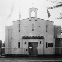 Image: street view of a white stone church flying Greek and Australian flags.