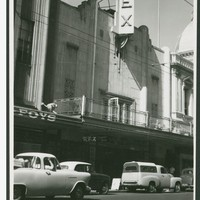 Image: Pedestrians and parked cars in front of a cinema
