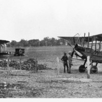 Image: bi-plane on ground with men standing nearby