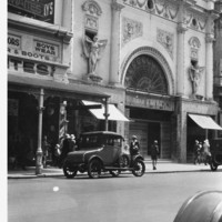 Image: Pedestrians and parked cars in front of ornate cinema facade