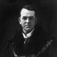 Image: A man with receeding dark hair and glasses poses for a portrait while wearing a dark robe and livery collar