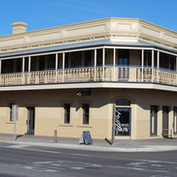 Image: A cream-coloured two-storey building with upstairs verandah. A sign over the front door reads 'McGrath's British Hotel'
