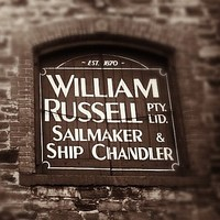 Image: Close-up photograph of part of an historic, multi-storey stone building. The words 'Est. 1870, William Russell Pty. Ltd., Sailmaker and Ship Chandler' are painted on the shutter of one of the building's second-floor windows