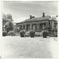 Image: Black and white photograph of the Anlaby house front lawn. House features mullioned windows, and deep set veranda supported by doric columns