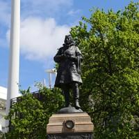 Image: Bronze statue of a man atop a granite pillar