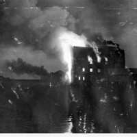 Image: A large, multi-storey building is completely consumed by fire. The blaze is taking place at night, and in close proximity to a river