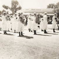 Group of women in white dresses and hats holding instruments.