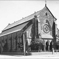 Image: A boy poses in front of the Baptist Church on the corner of Flinders Street and Divett Place. This church was built in 1861 to plans by Robert Thomas who also designed the Pilgrim Church. It features a rose window and front entrance with three arch