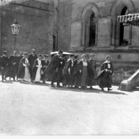 Image: A group of men and women in academic dress walk towards the entrance of Elder Hall on the way to their graduation ceremony