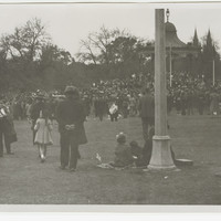 Image: a large group of men, women and children gather around a rotunda in a park