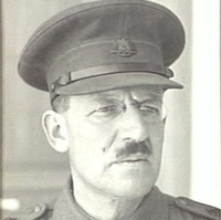 Image: A moustachioed middle-aged Caucasian man in an Australian Army officer's uniform. He is wearing a hat and spectacles with oval lenses