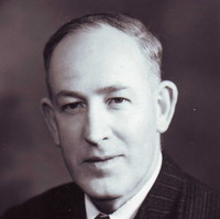 Image: A photographic head-and-shoulders portrait of a clean-shaven, middle-aged Caucasian man wearing a suit of 1940s vintage
