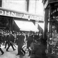Image: crowds of people, dressed fairly formally, in front of shop awnings