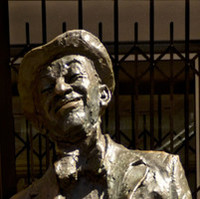 Image: bronze statue of smiling man leaning back with hands in pockets
