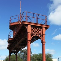 Image: A nineteenth-century iron gantry crowned by a wooden observation tower forms an archway over a modern carpark. An historic marker on a stone plinth is positioned next to the gantry