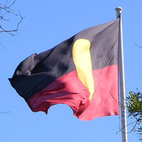 Image: flag with black top, red bottom and large yellow circle in the middle