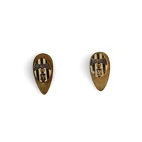 Image: two small metal pins in teardrop shape with black and white stripes