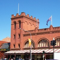 Image: A large brick building with archway windows and a square turret at one end. Cars drive by on a busy street in the foreground