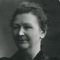 Image: A closeup portrait of a woman wearing a black dress with her hair tied back