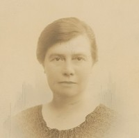 Image: A photographic head-and-shoulders portrait of a woman with ear-length dark hair and wearing 1920s attire