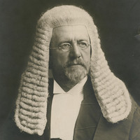 Image: A photographic head-and-shoulders portrait of a bearded middle-aged Caucasian man wearing a judicial wig and vestments. He is also wearing wire-rimmed spectacles and looking to his left