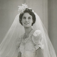 Image: A young Caucasian woman poses for a photograph in her 1940s vintage bridal gown